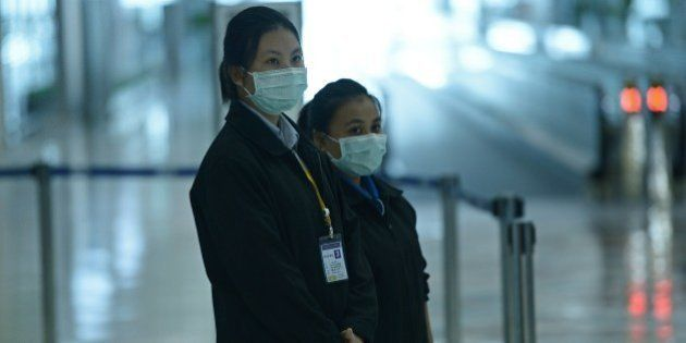 Airports of Thailand employees wear face masks as they wait for travelers to walk past a thermoscan checking...