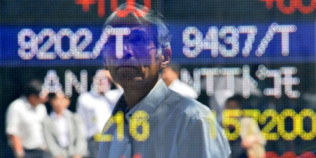 A pedestrian is reflected in the window as he looks at a quotation board flashing the Nikkei key index...