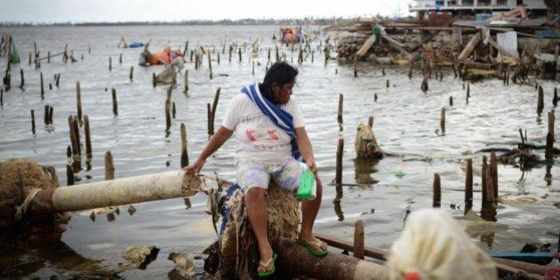 LEYTE, PHILIPPINES - NOVEMBER 20: A woman searches for usable materials on November 20, 2013 in Tacloban,...