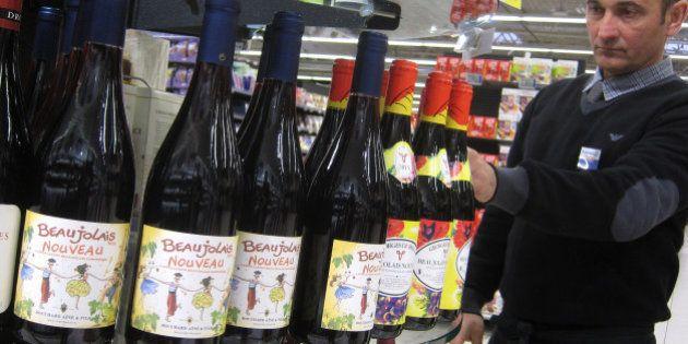 A shop assistant at a store in Nice, southeastern France, arranges bottles of 2013 Beaujolais Nouveau,...