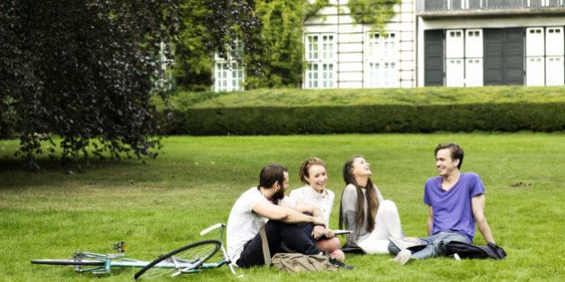 Four students sitting on the grass in a park, with some buildings in the background. Two female and two...