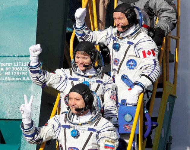 カザフスタンのバイコヌール宇宙基地で3日、ソユーズロケットに乗り込む(上から)カナダ、米国、ロシアの宇宙飛行士=ロイター