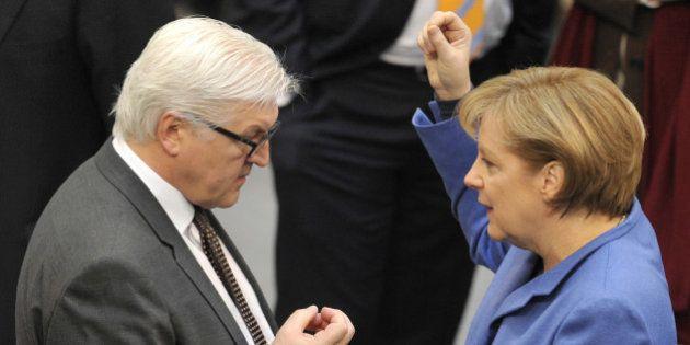 German Chancellor Angela Merkel speaks to Frank-Walter Steinmeier, leader of the Social Democratic Party's...