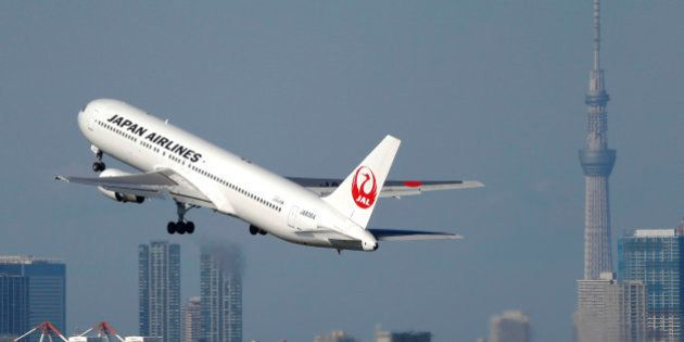 A Japan Airlines Co. (JAL) aircraft takes off from Haneda Airport while the Tokyo Sky Tree, right, stands...