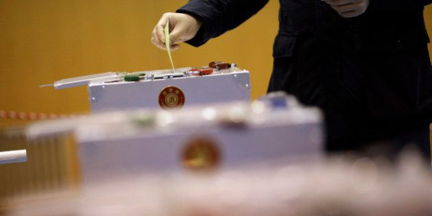 A man casts his vote in Japan's parliamentary elections at a polling station in Tokyo, Sunday, Dec. 14,...