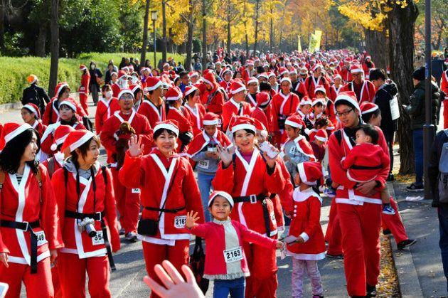 サンタ姿で大阪城公園を歩く参加者たち=大阪市中央区、朝日新聞社撮影