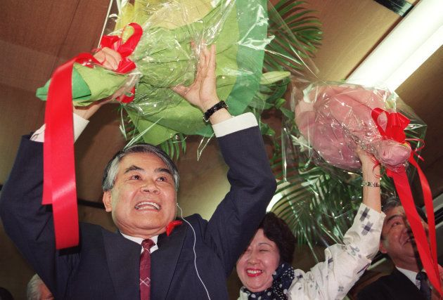 当選が確定し、花束を掲げて喜ぶ稲嶺恵一氏(沖縄・那覇市の選挙対策事務所)=1998年11月15日