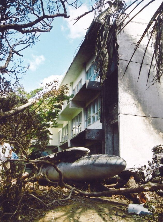 沖縄国際大学1号館付近に散らばった米軍ヘリコプターの残骸(ざんがい)を調べる米軍関係者(沖縄県宜野湾市)=2004年8月15日