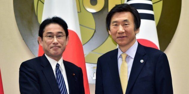 South Korean Foreign Minister Yun Byung-Se (R) shakes hands with his Japanese counterpart Fumio Kishida...