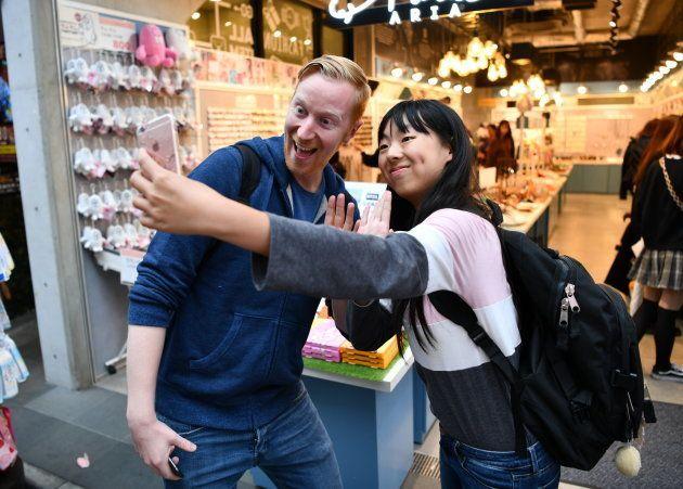ニュージーランドからの留学生(右)と記念撮影するヤバタン=東京・原宿