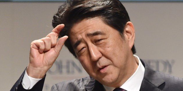 Japanese Prime Minister Shinzo Abe gestures as he delivers a speech at the first international symposium...
