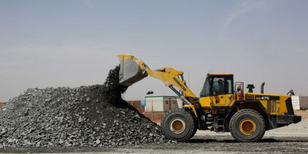 A Komatsu Ltd. front-loader bulldozer unloads gold-copper ore rocks taken from the underground pit at...
