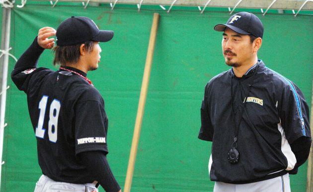 ブルペンで、ヤクルトから日本ハムに移籍した藤井秀悟(左)を指導する吉井理人投手コーチ(沖縄・名護市)