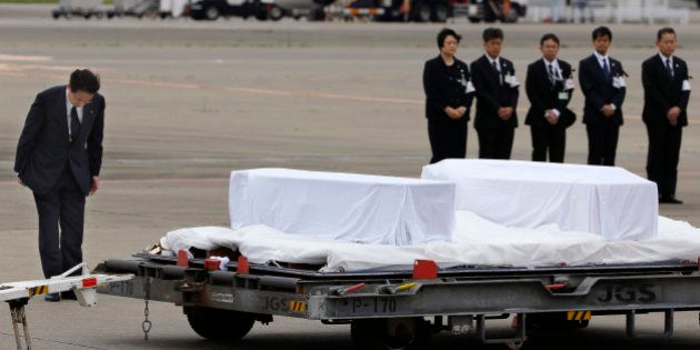 Japanese Foreign Minister Fumio Kishida, left, bows in front of the coffins of the victims who were killed...
