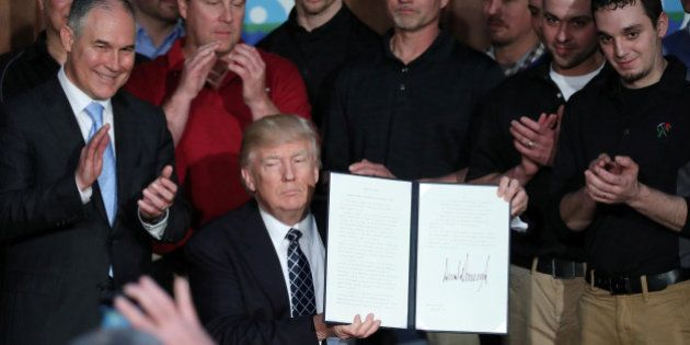 U.S. President Donald Trump holds up an executive order