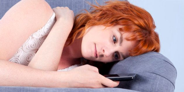Close-up of a cute young redhead lying on a sofa whilst