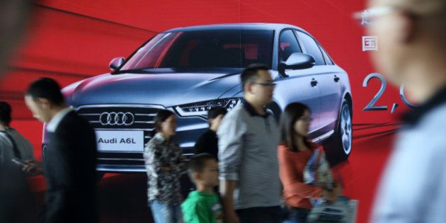Visitors walk past an advertisement for the Audi A6L sedan manufactured by FAW Audi, the joint venture...