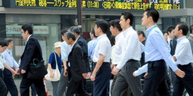 Businessmen cross an intersection, with stock prices seen on an electric market board in Tokyo, Wednesday,...