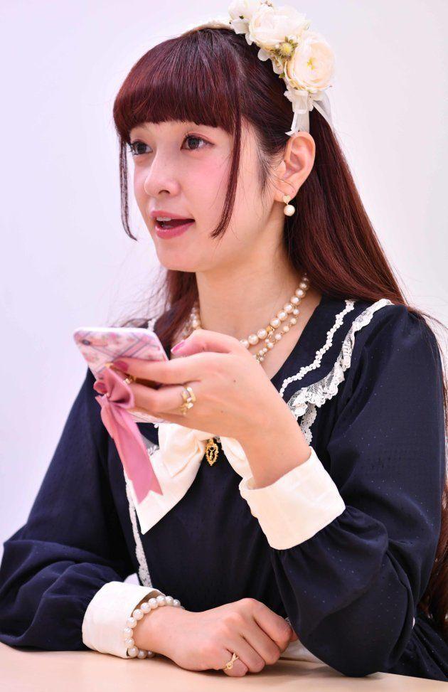 スマートフォンを片手にインタビューに応じる青木さん