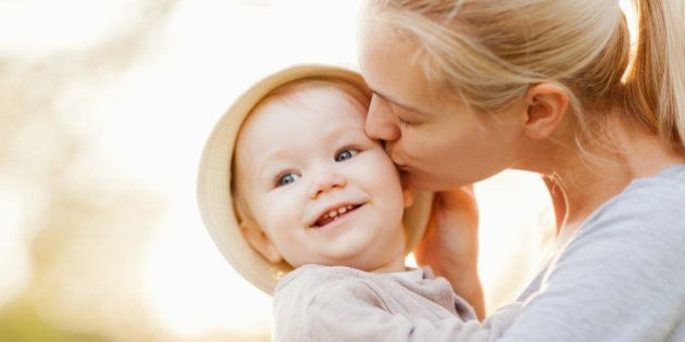 Close up of a beautiful young mother with blonde hair kissing her one year old daughter on the cheek....