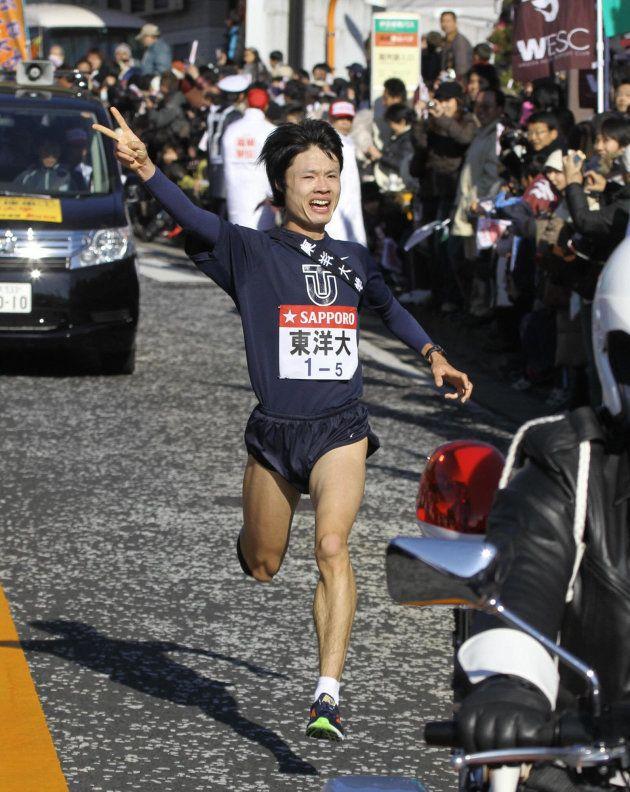 5区、ゴール目前で往路優勝を確信したかのようにVサインを見せる東洋大学の柏原竜二=2010年1月2日、神奈川県箱根町[代表撮影]