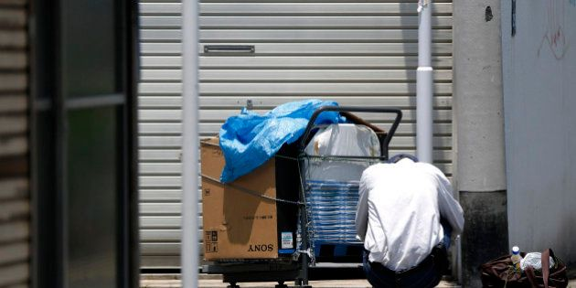 An elderly man squats next to a cart and a bag on a street in Tokyo, Japan, on Monday, July 8, 2013....