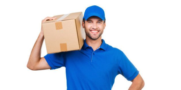 Joyful young courier carrying cardboard box on shoulder and smiling while standing against white