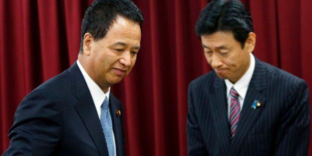 Akira Amari, Japan's minister of state for economic and fiscal policy, left, passes Yasutoshi Nishimura,...