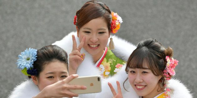 記念撮影をする新成人。(東京都練馬区の「としまえん」)