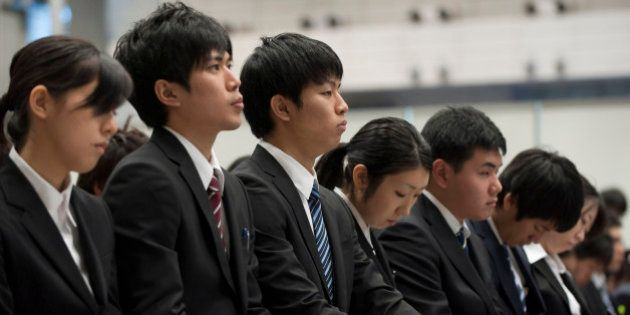 University students take notes as they attend a job fair hosted by Recruit Co. at Makuhari Messe in Chiba...