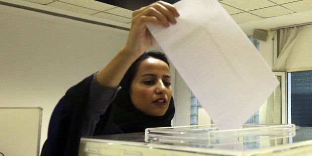 A Saudi woman casts her ballot at a polling center during municipal elections in Riyadh, Saudi Arabia,...