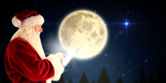 Santa uses a tablet PC against full moon over forest at
