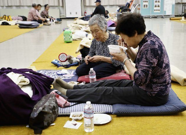 Residents from a quake-hit area eat their dinner at a shelter in Atsuma town, Hokkaido prefecture on...