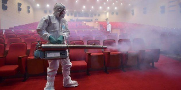 South Korean health officials fumigate a theater while wearing protective gear in Seoul on June 12, 2015....