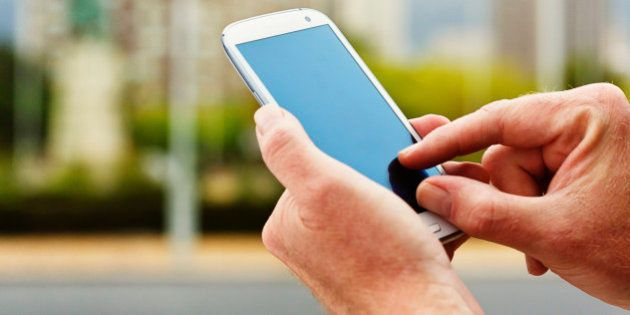 In a city street, a man's hands touch the blank screen on a modern cellphone with an android operating...