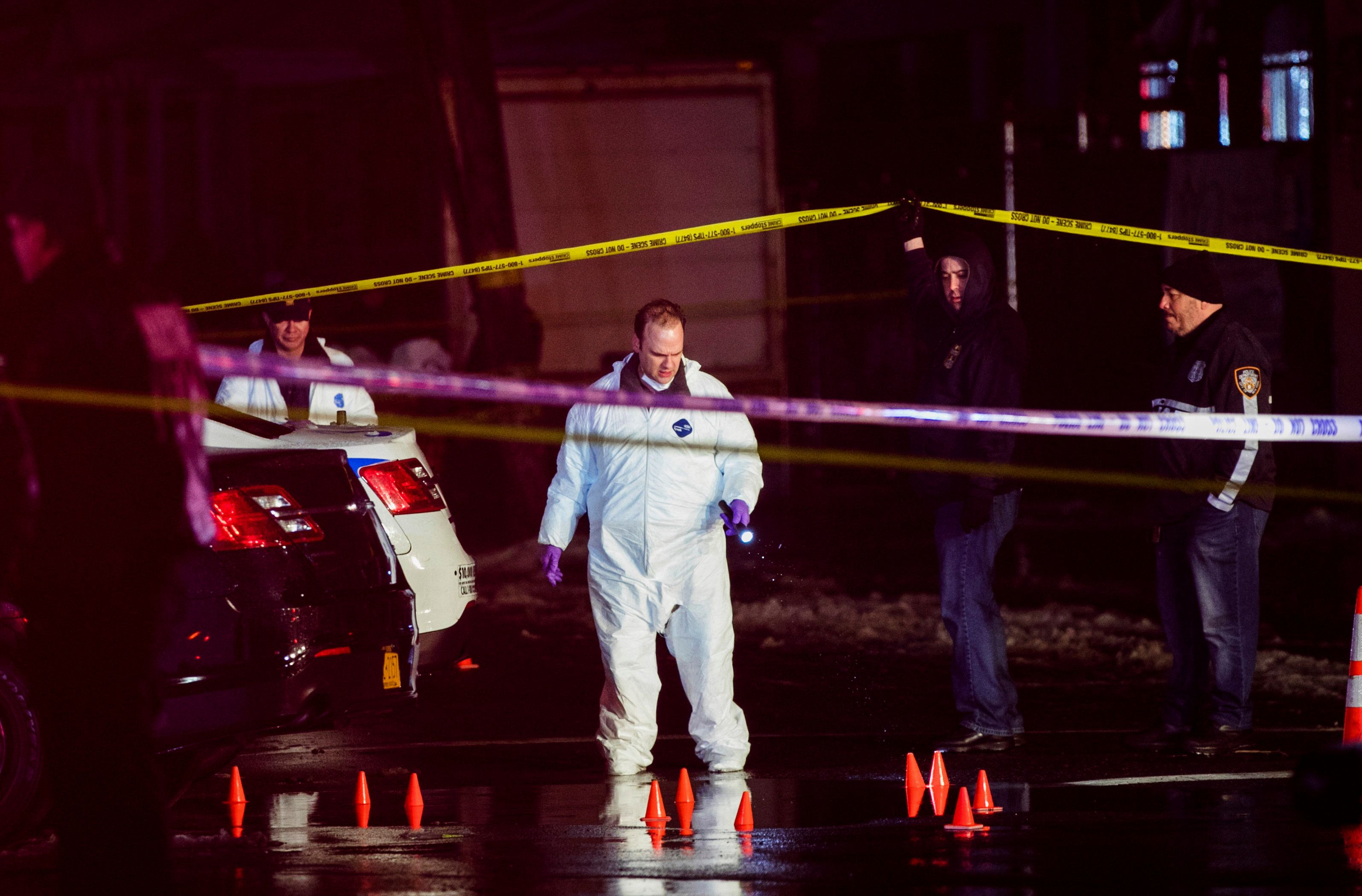 Investigators look over the area after New York City police officers were shot while responding to a robbery at a T-Mob
