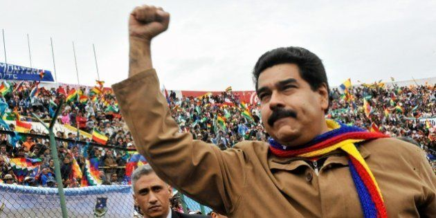 Venezuelan President Nicolas Maduro raises his fist as he arrives to a rally congregating thousands of...