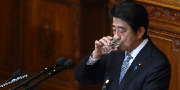 Shinzo Abe, Japan's prime minister, drinks a glass of water as he delivers a policy speech during an...