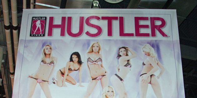 LAS VEGAS - JANUARY 09: Attendees walk under a banner for Hustler at the 2008 AVN Adult Entertainment...