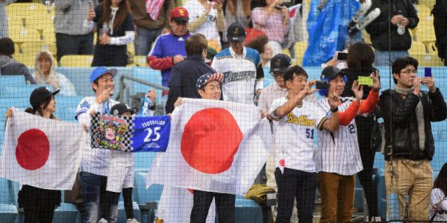 LOS ANGELES, CA - MARCH 21: Fans of team Japan take photos during warm ups before team Japan takes on...