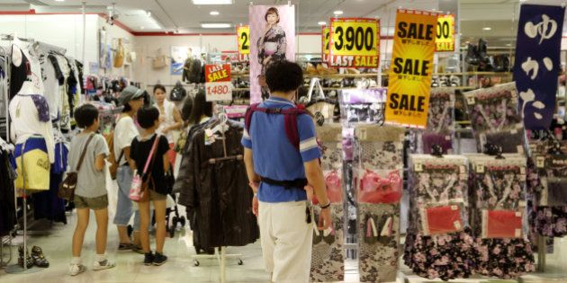 Customers shop in a store in the Odaiba area of Tokyo, Japan, on Monday, Aug. 12, 2013. Japan's economy...