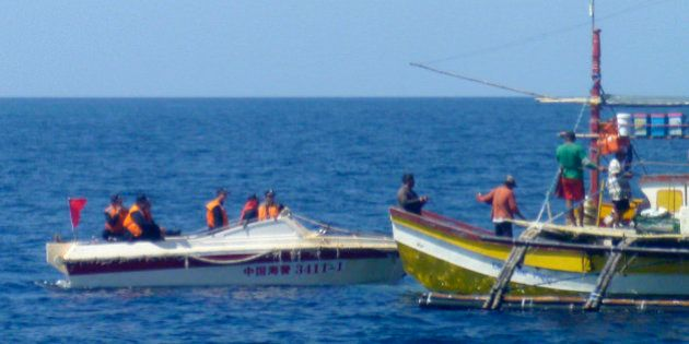 In this Feb. 27, 2015, photo, provided by Filipino fisherman Renato Etac, Chinese Coast Guard members...