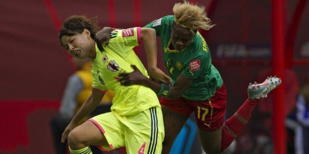 Japan defender Saki Kumagai (L) and Cameroon forward Gaelle Enganamouit fight for the ball during a Group...