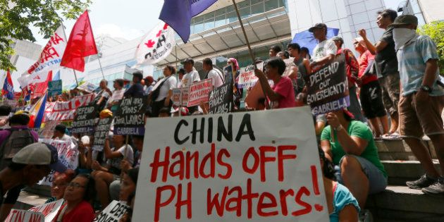 Protesters display placards during a rally outside of the Chinese Consulate hours before the Hague-based...