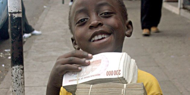A child poses with wads of Zimbabwean dollar notes begged on the streets of Harare Tuesday, Feb. 19,...