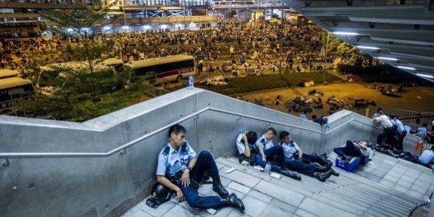 Policemen rest following pro-democracy protests in Hong Kong on September 29, 2014. Police fired tear...