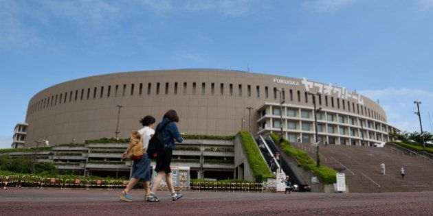 Pedestrians walk past the Yahuoku! Dome, operated by Fukuoka SoftBank Hawks Corp., in Fukuoka, Japan,...