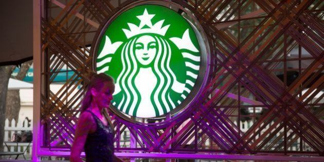 A woman walks by the logo of American coffee company and coffeehouse chain Starbucks coffee on the eve...