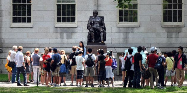 CAMBRIDGE, MA - JULY 30: People touring Harvard Yard stop by the John Harvard statue July 30, 2009 just...