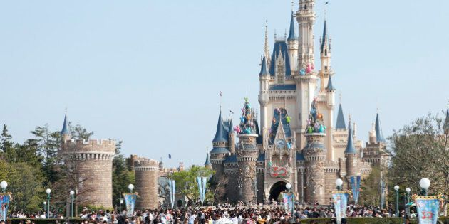 Visitors walk past the Cinderella Castle during 30th anniversary celebrations of Tokyo Disneyland, operated...